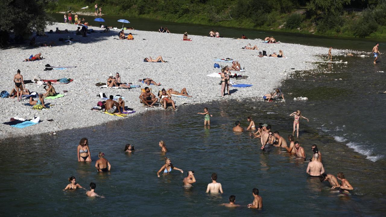 People enjoy the hot summer weather at the river Isar in Munich, Germany, Thursday, July 25, 2019. (AP Photo/Matthias Schrader)