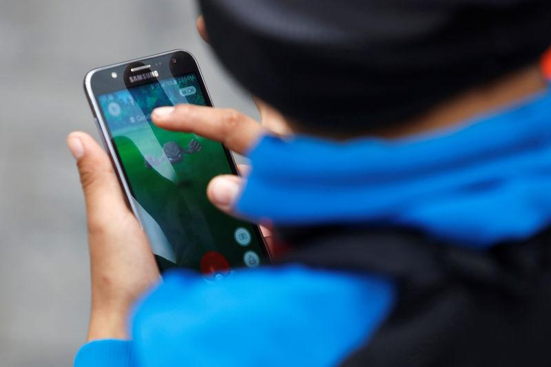 """A man plays the augmented reality mobile game """"Pokemon Go"""" at Kennedy park in Lima"""