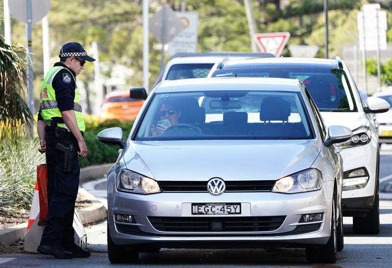 Motorists are seen at a checkpoint at Coolangatta on the Queensland- New South Wales border.