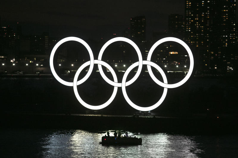 "People in a small boat view the Olympic rings in the Odaiba section of Tokyo, Thursday, March 12, 2020. Tokyo Governor Yuriko Koike spoke Thursday after the World Health Organization labeled the spreading virus a ""pandemic,"" a decision almost certain to affect the Tokyo Olympics. (AP Photo/Jae C. Hong)"