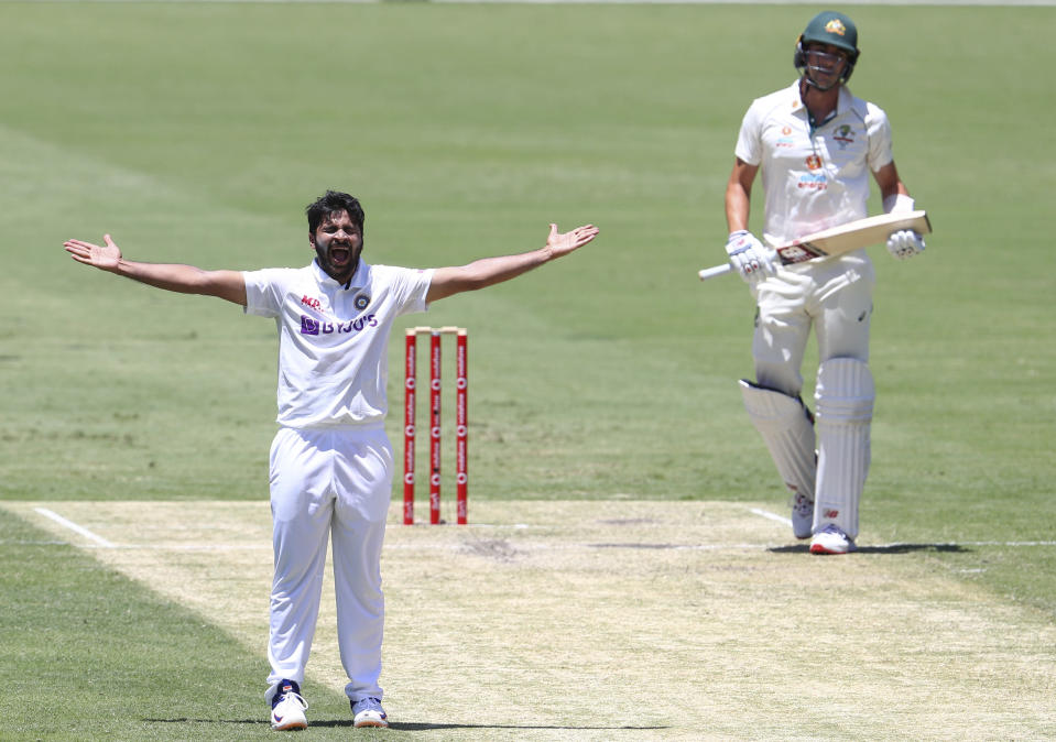 India's Shardul Thakur, left, appeals successfully for the wicket of Australia's Pat Cummins, right, during play on day two of the fourth cricket test between India and Australia at the Gabba, Brisbane, Australia, Saturday, Jan. 16, 2021. (AP Photo/Tertius Pickard)