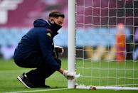 A groundsperson cleans the goalpost ahead of the Premier League football match between Aston Villa and Sheffield United