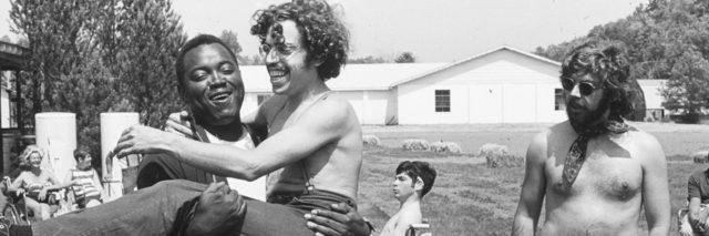 Still image from the documentary Crip Camp showing a young black man carrying a young white man while another white man with long hair and a beard watches