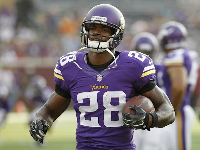 In this Aug. 16, 2014, photo, Minnesota Vikings running back Adrian Peterson (28) warms up before a NFL preseason football game against the Arizona Cardinals in Minneapolis.Millions of people using the top three fantasy football platforms have generated three different answers to the question of that top draft pick. Yahoo says LeSean McCoy of Philadelphia. ESPN says Adrian Peterson. CBS Sports says it's Jamaal Charles of Kansas City. (AP Photo/Ann Heisenfelt)