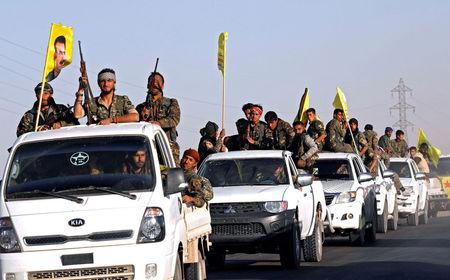 Fighters of Syrian Democratic Forces ride on trucks as their convoy passes in Ain Issa, Syria October 16, 2017. REUTERS/Erik De Castro