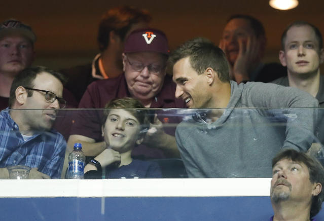 Minnesota Vikings quarterback Kirk Cousins, right, who played at Michigan State, talks with others while watching the first half of an East Regional semifinal in the NCAA men's college basketball tournament between LSU and Michigan State, Friday, March 29, 2019, in Washington. (AP Photo/Alex Brandon)
