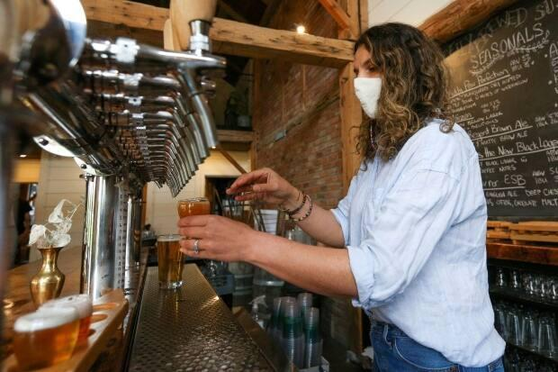 Parsons Brewing Company owner Samantha Parsons pours a beer at the brewery in Picton, Ont. The business is one of those now requiring proof of vaccination. (Lars Hagberg/Reuters - image credit)