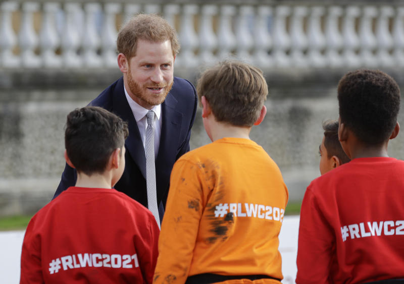 Britain's Prince Harry greets schoolchildren in the gardens at Buckingham Palace in London, Thursday, Jan. 16, 2020. Prince Harry, the Duke of Sussex will host the Rugby League World Cup 2021 draw at Buckingham Palace, prior to the draw, The Duke met with representatives from all 21 nations taking part in the tournament, as well as watching children from a local school play rugby league in the Buckingham Palace gardens. (AP Photo/Kirsty Wigglesworth)