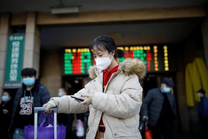 Woman wearing a face mask uses her cellphone as she walks outside Beijing Railway Station as the country is hit by an outbreak of the new coronavirus, in Beijing