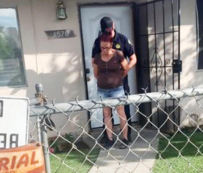 This Monday, April 22, 2019, photo taken by a Riverside County Animal Services officer shows the arrest of Deborah Sue Culwell at her Coachella, Calif., home. The California woman could face up to seven years behind bars on a slew of charges filed Tuesday after authorities say surveillance video showed her casually tossing a bag of 3-day-old puppies into a trash can on a sweltering day. (Riverside County Animal Services via AP)