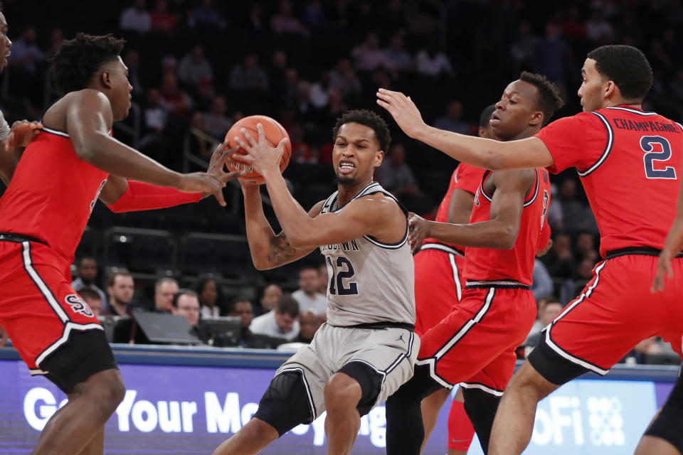 Georgetown guard Terrell Allen (12) is surrounded by St. John's defenders during the first half of an NCAA college basketball game in the first round of the Big East men's tournament Wednesday, March 11, 2020, in New York. (AP Photo/Kathy Willens)