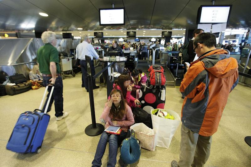 Alaska Airlines passengers wait in a line near inoperable check-in computers, Monday, Oct. 8, 2012, at Seattle-Tacoma International Airport in Seattle during a system-wide outage of the computers the airline uses to check in passengers. The computers Alaska Airlines uses to check in passengers stopped working at 7:40 a.m. Monday, causing long lines of frustrated passengers who were unable to board flights that were delayed. (AP Photo/Ted S. Warren)