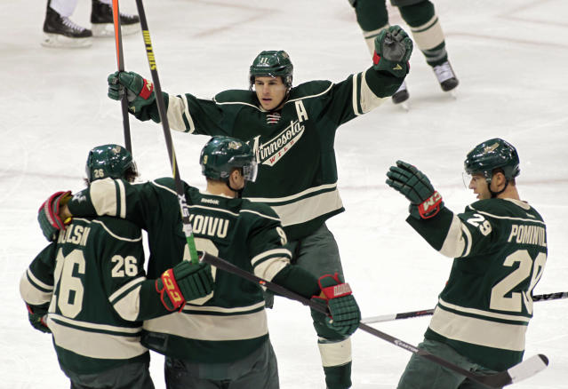 Minnesota Wild center Mikko Koivu (9) of Finland, is congratulated by teammates Matt Moulson (26), Zach Parise (11), and Jason Pominville (29) after scoring a power play goal during the first period of an NHL hockey game, Saturday, March 22, 2014, in St. Paul, Minn. (AP Photo/Paul Battaglia)