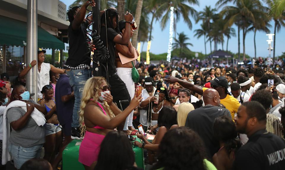MIAMI BEACH, FLORIDA - MARCH 21: People enjoy themselves along Ocean Drive on March 21, 2021 in Miami Beach, Florida. College students have arrived in the South Florida area for the annual spring break ritual, prompting city officials to impose an 8pm to 6am curfew as the coronavirus pandemic continues. Miami Beach police have reported hundreds of arrests and stepped up deployment to control the growing spring break crowds. (Photo by Joe Raedle/Getty Images)