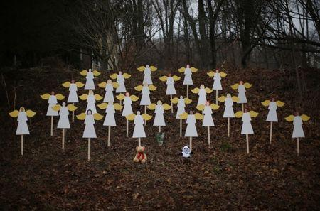 Twenty-seven wooden angel figures are seen placed in a wooded area beside a road near the Sandy Hook Elementary School for the victims of a school shooting in Newtown, Connecticut December 16, 2012. REUTERS/Mike Segar