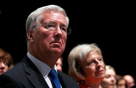 Britain's Defence Secretary Michael Fallon (L) and Home Secretary Theresa May listen to Prime Minister David Cameron deliver his keynote address at the annual Conservative Party Conference in Manchester, Britain October 7, 2015. REUTERS/Suzanne Plunkett