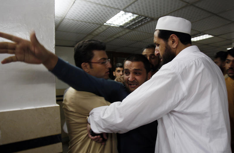 People comfort a man at a local hospital, who lost two cousins in an attack in Peshawar, Pakistan on Monday, April 29, 2013. A suicide bomber targeting policemen killed many people in northwestern Pakistan on Monday in the latest attack ahead of next month's parliamentary election, police said. (AP Photo/Mohammad Sajjad)