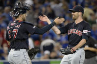 Cleveland Indians starting pitcher Shane Bieber celebrates with teammate Kevin Plawecki (27) after pitching a complete game shutout against the Toronto Blue Jays after a baseball game, Wednesday, July 24, 2019 in Toronto. (Nathan Denette/Canadian Press via AP)