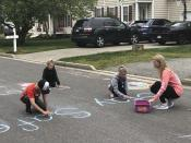 Jamie Burton, of Glen Allen, Va., and her three children, left to right, Carter, Cayden and Josie, write chalk messages to their neighbors as they stay at home during the coronavirus outbreak, Thursday, March 26, 2020. (AP Photo/Denise Lavoie)