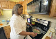 In this May 2021 image taken by Crystal Jackson, Lori Jackson cooks a steak and asparagus recipe she found from TikTok at her home in Lynn, Mass. Since the pandemic, TikTok has become a place for people to find new recipe ideas as well as burgeoning celebrity chefs. (Crystal Jackson via AP)