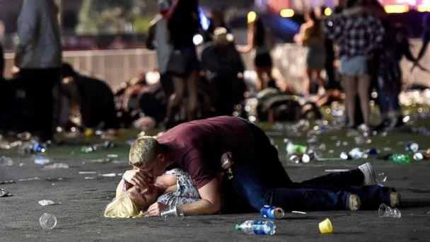 PHOTO: A man lays on top of a woman as others flee the Route 91 Harvest country music festival grounds after an active shooter was reported on Oct. 1, 2017 in Las Vegas. The woman later was seen getting up with help. (David Becker/Getty Images)