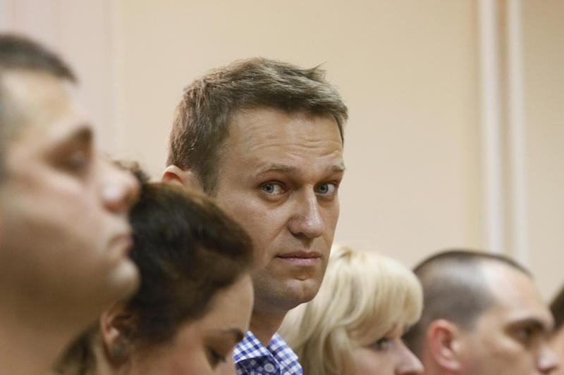 Russian opposition leader Alexei Navalny, center, and his former colleague Pyotr Ofitserov, foreground left, react while listening to judge Sergei Blinov in a court in Kirov, Russia Thursday, July 18, 2013. Alexei Navalny, one of the Russian opposition's leading figures, has been sentenced to five years in prison. Navalny was sentenced after being found guilty of embezzlement Thursday in a case that he and his supporters claimed was politically driven to try to shut down the vehement Kremlin critic and intimidate his supporters. (AP Photo/Dmitry Lovetsky)