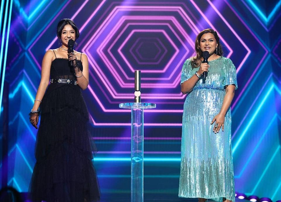"""SANTA MONICA, CALIFORNIA – NOVEMBER 15: 2020 E! PEOPLE'S CHOICE AWARDS — In this image released on November 15, (L-R) Maitreyi Ramakrishnan and Mindy Kaling of """"Never Have I Ever"""", The Comedy Show of 2020, accept the award onstage for the 2020 E! People's Choice Awards held at the Barker Hangar in Santa Monica, California and on broadcast on Sunday, November 15, 2020. (Photo by Christopher Polk/E! Entertainment/NBCU Photo Bank via Getty Images)"""
