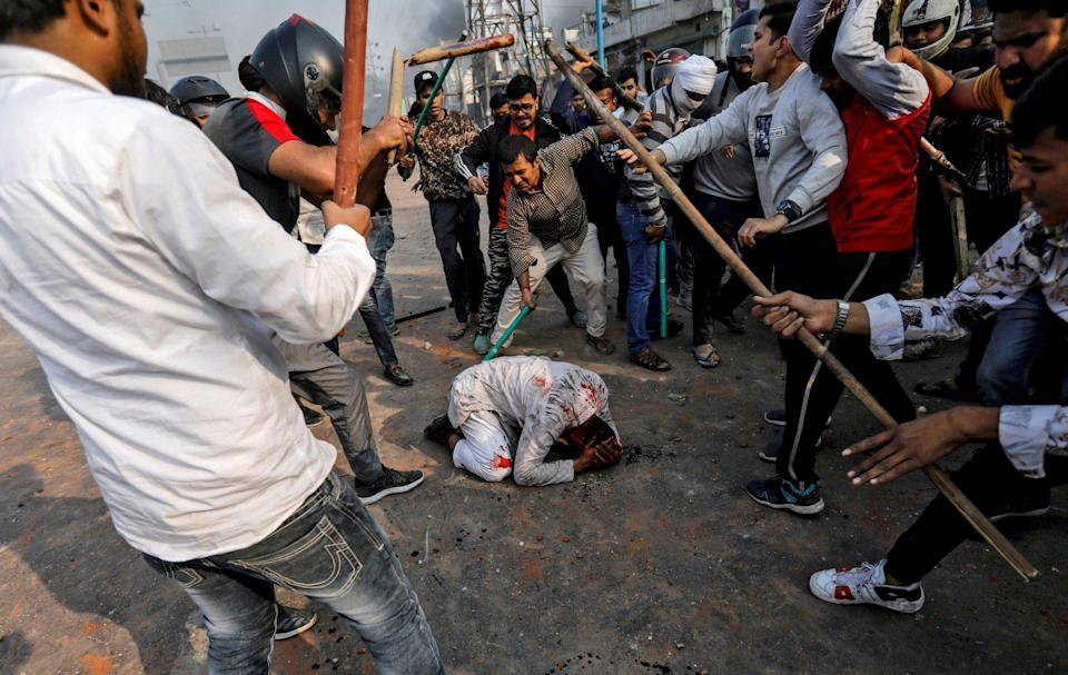 Hindu nationalists beat a Muslim man, Mohammad Zubair, during protests in New Delhi in February 2020: Siddiqui, who was forced to flee the situation, later tracked the man down to apologise for leaving him to his fate - Danish Siddiqui/Reuters