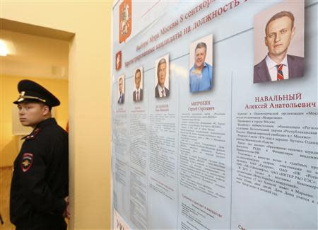 A policeman stands near a list of mayoral candidates during voting at a polling station in Moscow September 8, 2013. REUTERS/Sergei Karpukhin