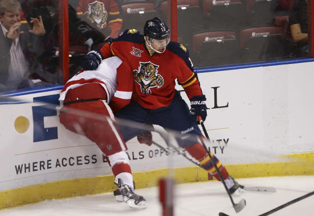 Florida Panthers' Jimmy Hayes (12) tries to control Detroit Red Wings' Jakub Kindl (4) and the puck during the first period of a NHL hockey game in Sunrise, Fla., Tuesday, Dec. 10, 2013. (AP Photo/J Pat Carter)