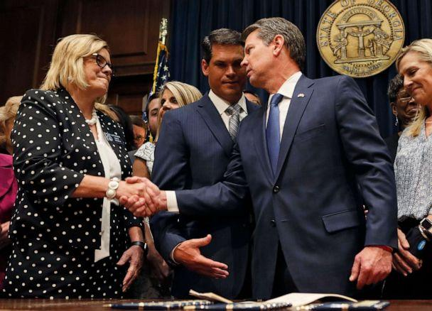 PHOTO: Georgia Gov. Brian Kemp shakes hands with state Sen. Renee Unterman after signing legislation banning abortions once a fetal heartbeat can be detected, in Atlanta, May 7, 2019. (Bob Andres/Atlanta Journal-Constitution via AP)