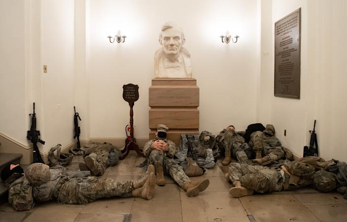 Members of the National Guard take a rest in the Rotunda of the Capitol, near a bust of Abraham Lincoln