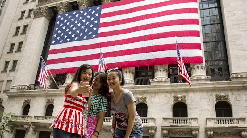 Chinese tourists take photographs of themselves outside of the New York Stock Exchange shortly after the opening bell in New York