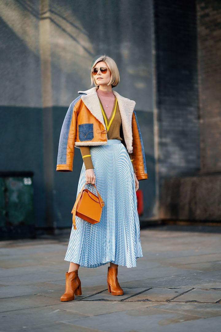 <p>A guest photographed during London Fashion Week in a cropped aviator jacket, periwinkle blue midi skirt and tinted sunnies. <em>[Photo: Getty]</em> </p>