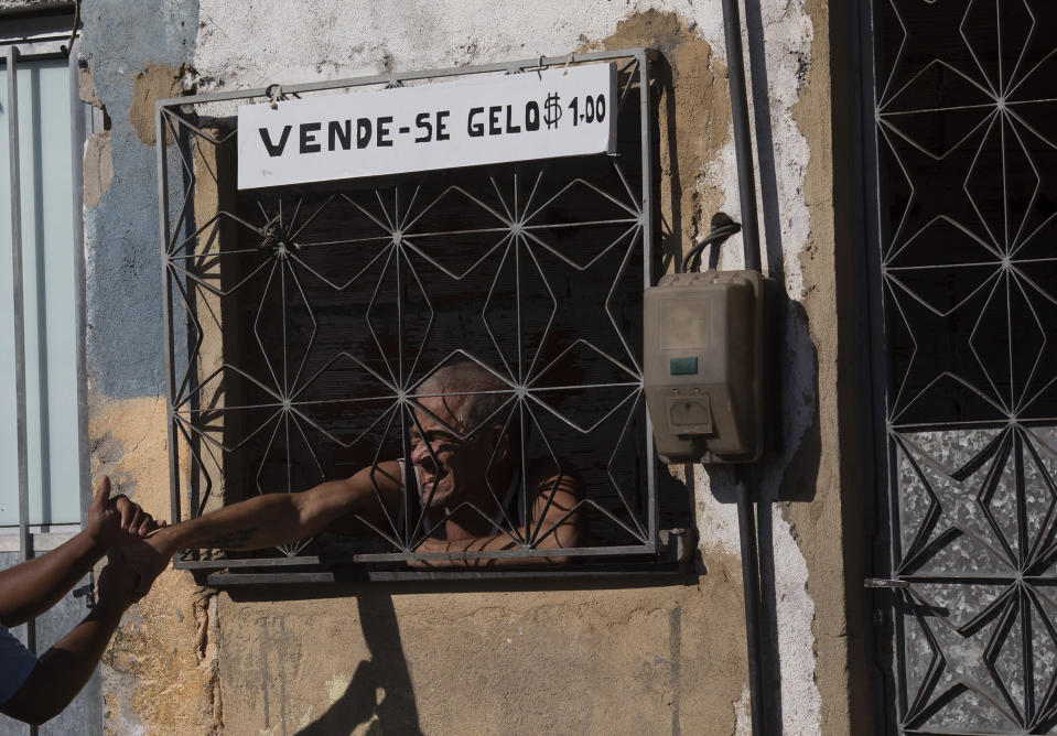"""A resident greets a water utility worker from CEDAE through his home's window, where he has a sign that reads in Portuguese """"Ice for sale,"""" as water workers disinfect the Mare Complex slum in an effort to curb the spread of the new coronavirus, in Rio de Janeiro, Brazil, Monday, May 4, 2020. (AP Photo/Silvia Izquierdo)"""