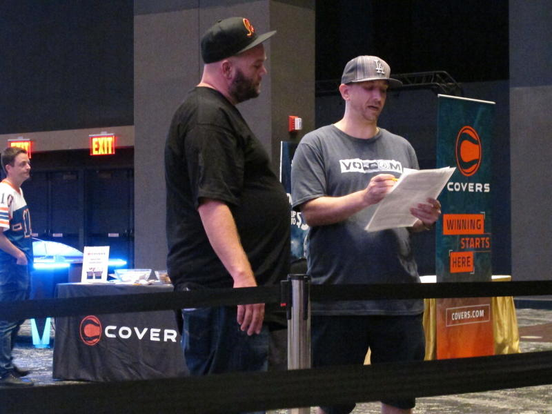 This Sept. 5, 2019 photo shows customers at the sports book at Bally's casino in Atlantic City, N.J. checking sheets listing the odds on that night's games. Figures released Sept. 12, 2019 show more than $293 million was wagered on sports in New Jersey in August, helping Atlantic City's nine casinos increase their revenue by 13% compared to a year ago. (AP Photo/Wayne Parry)