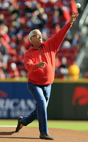 This Oct. 10, 2012, photo shows Cincinnati Reds broadcaster Marty Brennaman throwing out a ceremonial first pitch in Cincinnati. Brennaman says the Cincinnati Reds opening day festivities are unlike any other major league city. People are getting ready for Monday's events and the opening game with the Los Angeles Angels. (AP Photo/Al Behrman)
