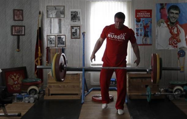 Olympic silver medallist weightlifter Dmitry Klokov drops weights during training at his father's house in the village of Sinkovo outside Moscow, April 3, 2012.