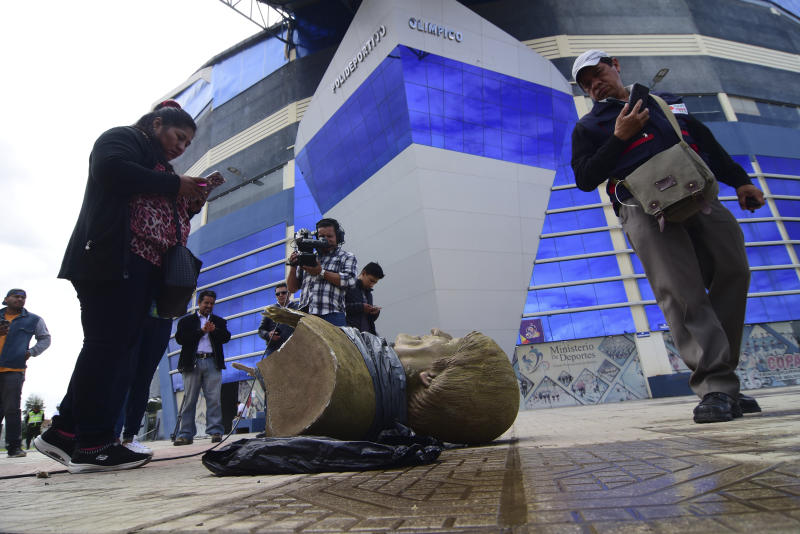 In this Jan. 13, 2020 photo, members of the media take images of a destroyed bust of Bolivia's former President Evo Morales, after it was knocked down on the orders of Bolivia's sports minister, outside a sports center in Cochabamba, Bolivia. Across Bolivia, the government of interim President Jeanine Áñez is taking down statues, painting over murals, changing the names of soccer fields and stadiums, and trying to erase the legacy of the former leader, who ruled the Andean country for more than 14 years as its first indigenous president. (Daniel James/Los Tiempos via AP)