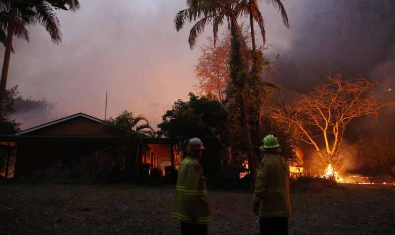 A bushfire in Hillville moves in on a house near the Pacific Highway, north of Nabiac in the Mid North Coast region of NSW on Tuesday. Source: AAP