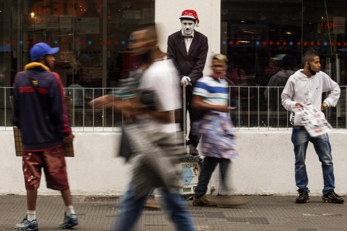 """A street performer dressed as Charlie Chaplin stands still as he works for tips from shoppers along the street """"25 de Marco"""" days before a COVID-19 lockdown goes into effect in Sao Paulo, Brazil, Wednesday, Dec. 23, 2020. Only essential business will be allowed to operate from Dec. 25 - 27 and Jan. 1 - 3. (AP Photo/Carla Carniel)"""