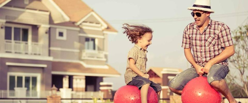 Dad and son jumping on inflatable balls on the lawn in front of house at the day time