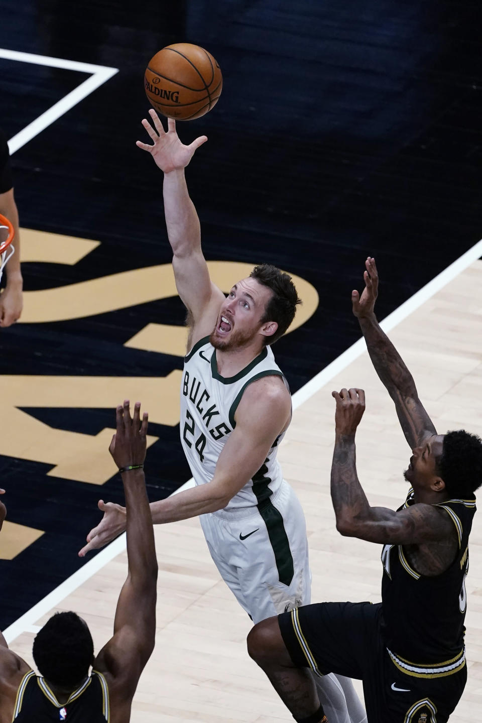 Milwaukee Bucks guard Pat Connaughton (24) goes in for a basket as Atlanta Hawks guard Lou Williams, right, defends during the first half of an NBA basketball game Thursday, April 15, 2021, in Atlanta. (AP Photo/John Bazemore)