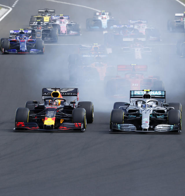 Red Bull driver Max Verstappen, left, of the Netherlands, and Mercedes driver Valtteri Bottas, of Finland, challenge for the first position after starting during the Hungarian Formula One Grand Prix at the Hungaroring racetrack in Mogyorod, northeast of Budapest, Hungary, Sunday, Aug. 4, 2019. (AP Photo/Laszlo Balogh)