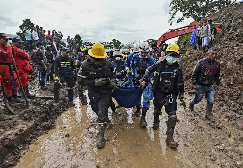 Rescuers carry away a body found under the mud in Rosas, southwest Colombia, following the mudslide provoked by heavy rains