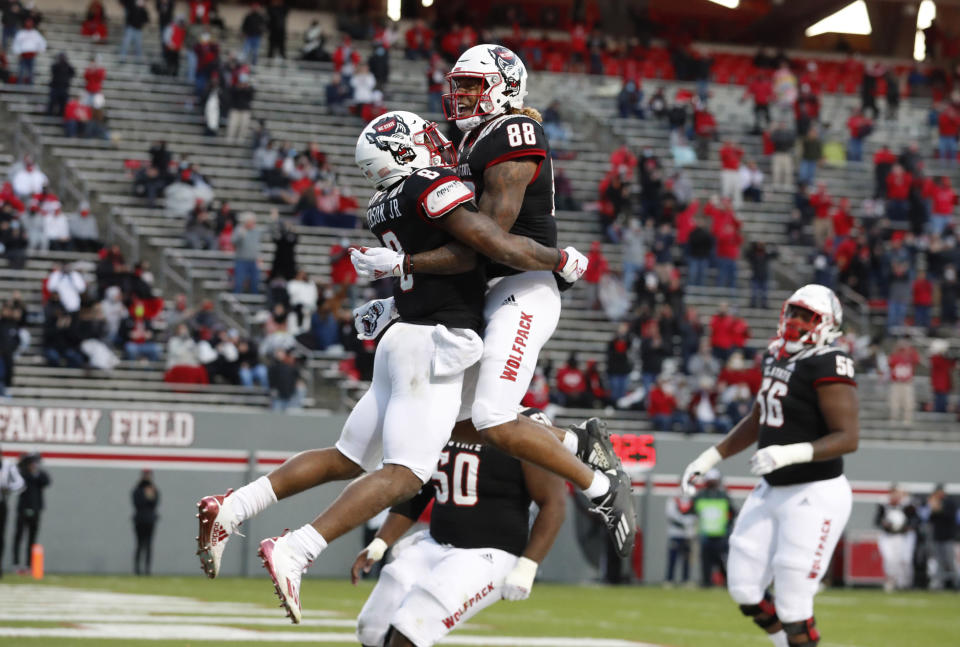 North Carolina State running back Ricky Person Jr. (8) celebrates with Devin Carter (88) after scoring on a 20-yard touchdown run against Georgia Tech during the first half of an NCAA college football game in Raleigh, N.C., Saturday, Dec. 5, 2020. (Ethan Hyman/The News & Observer via AP, Pool)