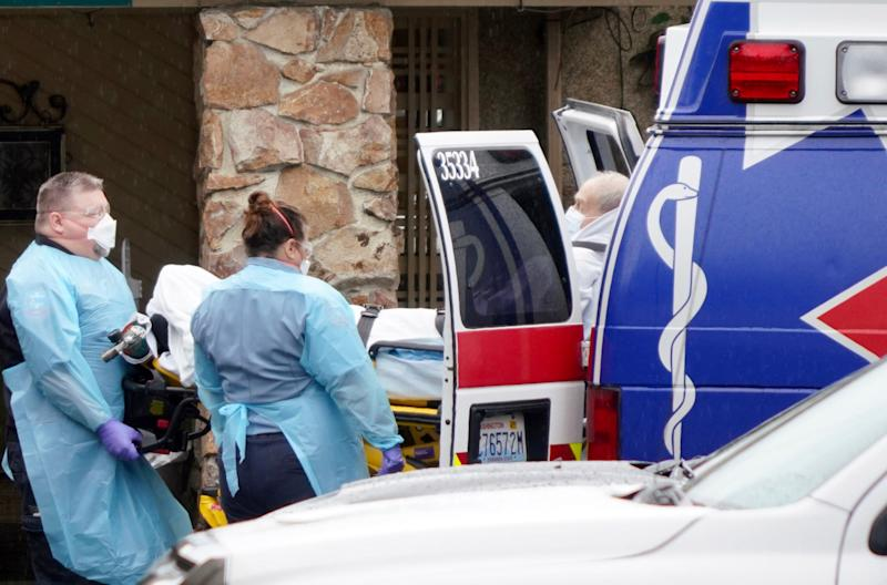 Medical workers load a sick patient into the back of a waiting ambulance for transport to a hospital from the Life Care Center of Kirkland, Wash., during the coronavirus outbreak.
