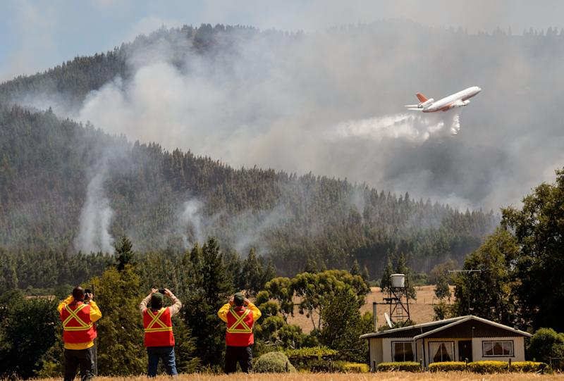 An air tanker carrier flies over a forest fire in Galvarino, Chile, on February 8, 2019. Fueled by extreme heat, forest fires in Chile have killed two people, injured another two and burned more thousands of acres.