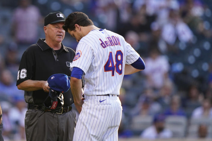 New York Mets starter Jacob deGrom (48) unbuckles his belt for third base umpire Ron Kulpa (46) after leaving the mound after pitching the top of the fifth inning of a baseball game against the Atlanta Braves, Monday, June 21, 2021, in New York. (AP Photo/Kathy Willens)