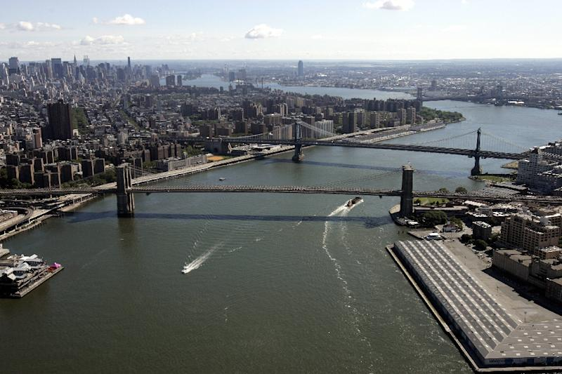 View of the Brooklyn Bridge (foreground) and Manhattan Bridge spanning New York's East River where at least two people died when a helicopter carrying six people including the pilot crashed into the river